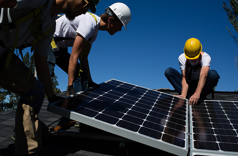 Technicians install solar panels on a home in Spokane, Washington.