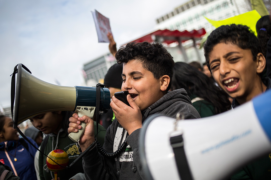 Adam Abdo Alshuga (right), 11-years-old, marches alongside Zakaria Homran (left), 13-years-old, with a megaphone. The two are students at Oakland's Urban Promise Academy.