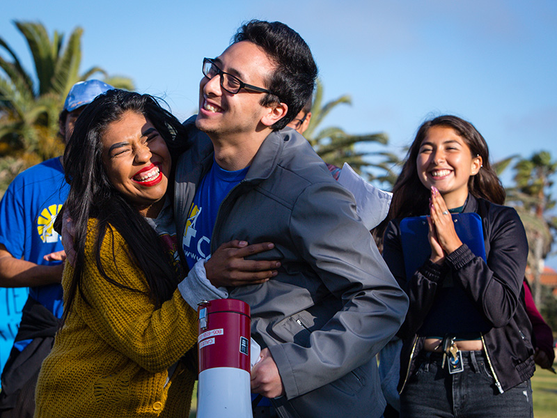 CAUSE policy and communications director director Lucas Zucker (right) hugs a fellow advocate at a celebration marking the end of the Puente Power plant.