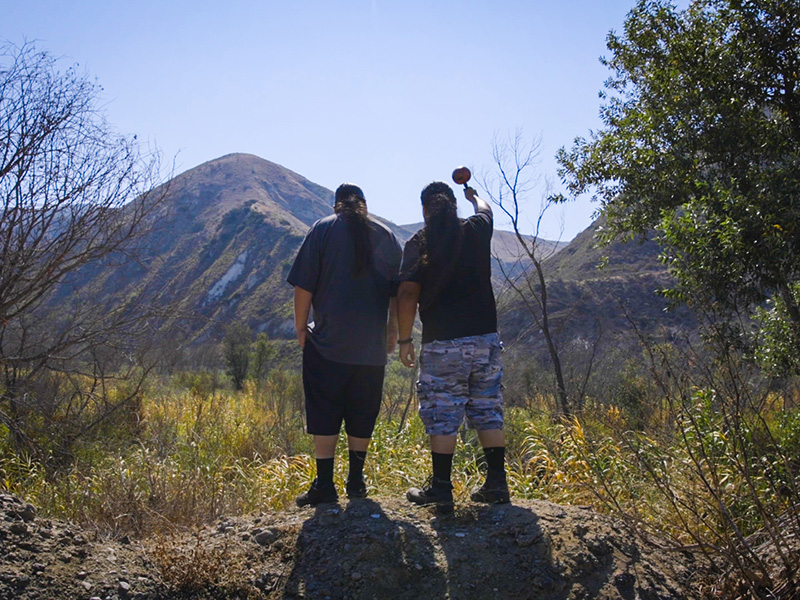 Sergio Valenzuela and Kote-Yakez Melendez, members of the Wishtoyo Foundation, look out over the Santa Clara River, or Utom, where a gas plant is proposed.