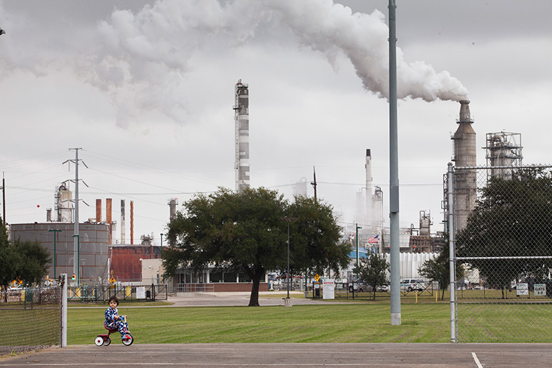 Chrisangel, then 3-years-old, rides his tricycle in Hartman Park, Nov. 21, 2013, in Houston in the Manchester neighborhood. The Valero refinery is in the background. Chrisangel and his family live on the perimeter of the park.