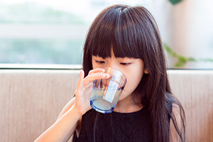 A child drinks a glass of water. (VisionChina / Getty Images)