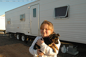 Brianna Edson, a Mississippi resident, and her new dog Dixie in front of the travel trailer serving as their temporary home along with Brianna's mother Wendy (not pictured) at the Ingalls-Wright Emergency Group Site, in November 2005. (Mark Wolfe / FEMA)