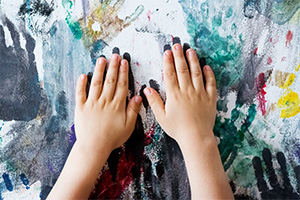 A child plays with house paint. (Dedi Grigoroiu / Shutterstock)