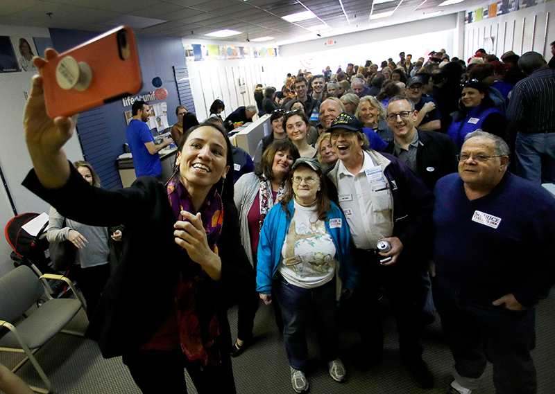 House candidate Sharice Davids takes a photo with supporters during a rally at her campaign office on Nov. 3, 2018, in Overland Park, Kan. Davids challenged Incumbent Republican U.S. Rep. Kevin Yoder for Kansas' 3rd Congressional District seat, and won her election bid.