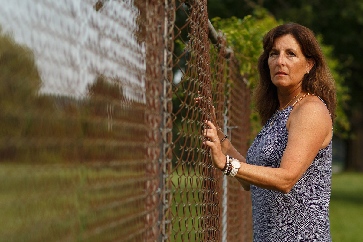Hope Gross stands next to the Naval Air Warfare Center in Warminster, Pennsylvania, where PFAS-laden firefighting foam poisoned local streams.