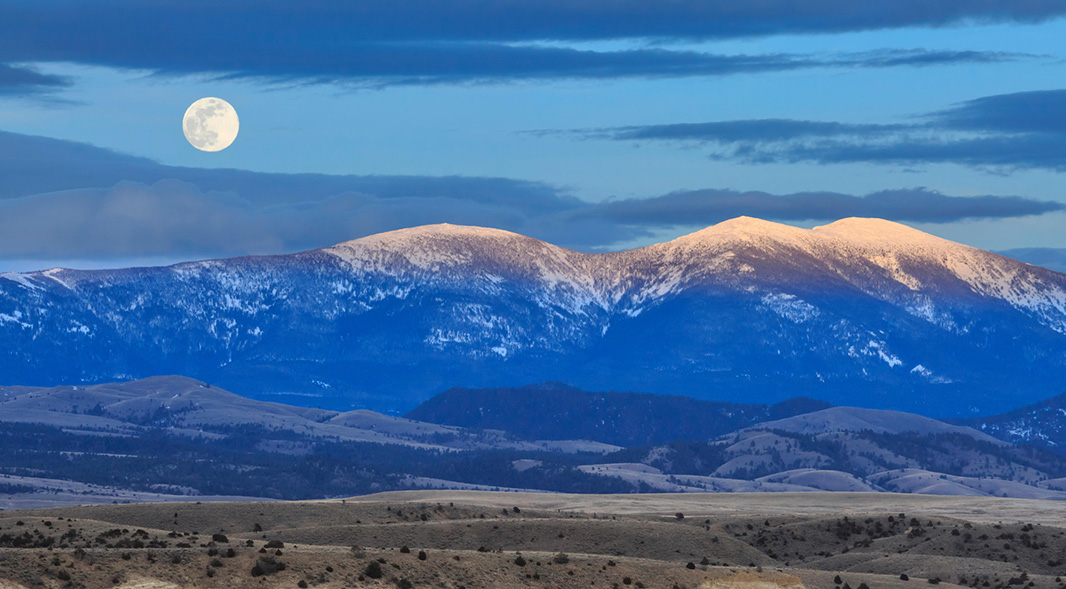 A full moon is seen above Mount Baldy in the Big Belt Mountains near Townsend, Montana, April 2019. Nearby land was recently protected by a federal judge's ruling; however, the Big Belt Mountains are still at risk.