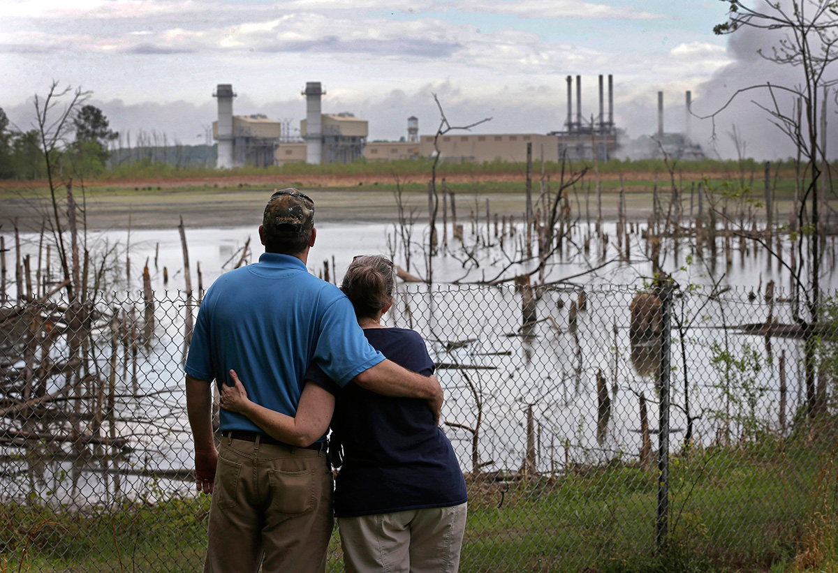 A couple in Dukeville, N.C., looks across a coal ash pond full of dead trees. North Carolina has ordered Duke Energy to close all its coal ash ponds in the state.