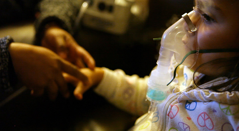 A mother comforts a child receiving treatment for asthma in Southern California.