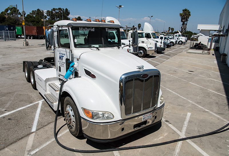 An electric hybrid heavy duty truck, used to move freight at the Port of Long Beach in California, is plugged in to charge.