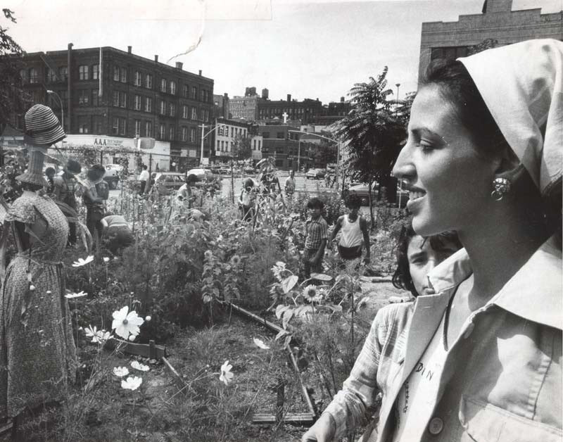 Black and white archival photo of Liz Christy and a group of youth standing in the rows of flowers in the Liz Christy Community Garden in Manhattan.