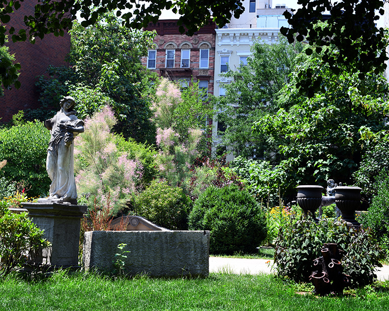 A variety of perennial plants and stone sculptures beside a lawn of grass in the Elizabeth Street Garden in Manhattan.