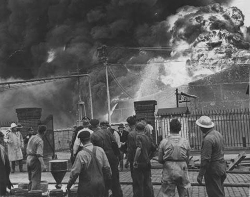 Firefighters and volunteers are helpless onlookers as they survey the billowing black smoke and flames from the 1944 East Ohio Gas Company explosion.