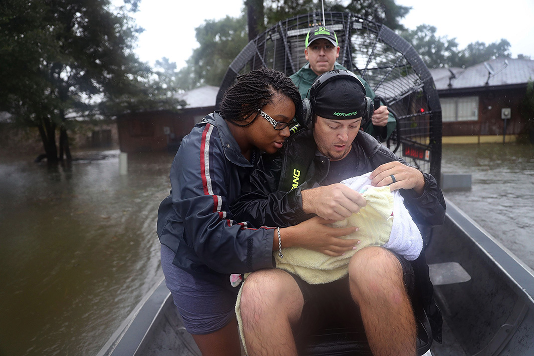 Shardea Harrison looks on at her 3-week-old baby being held by airboat rescuers who ferried the family from their flooded home.