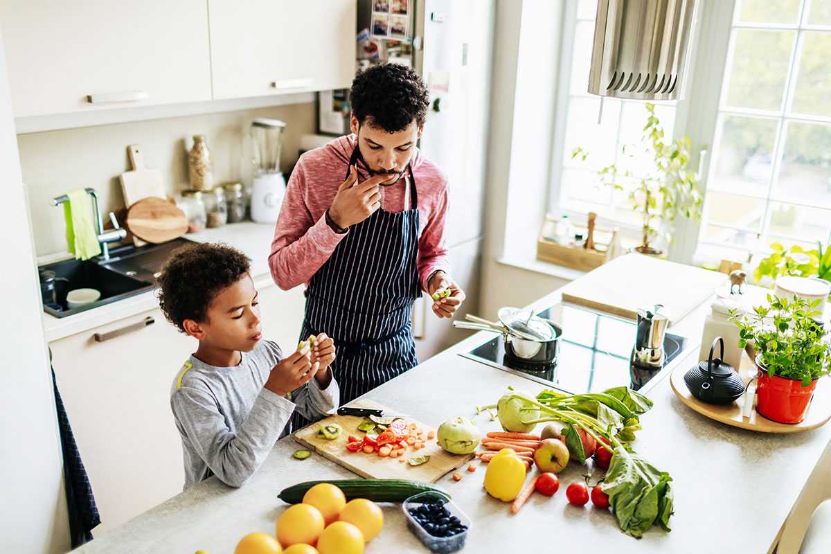 A father prepares a meal with his son on an induction stove. Children who grow up in a home with a gas stove are 42% more likely to develop asthma than those who don't.