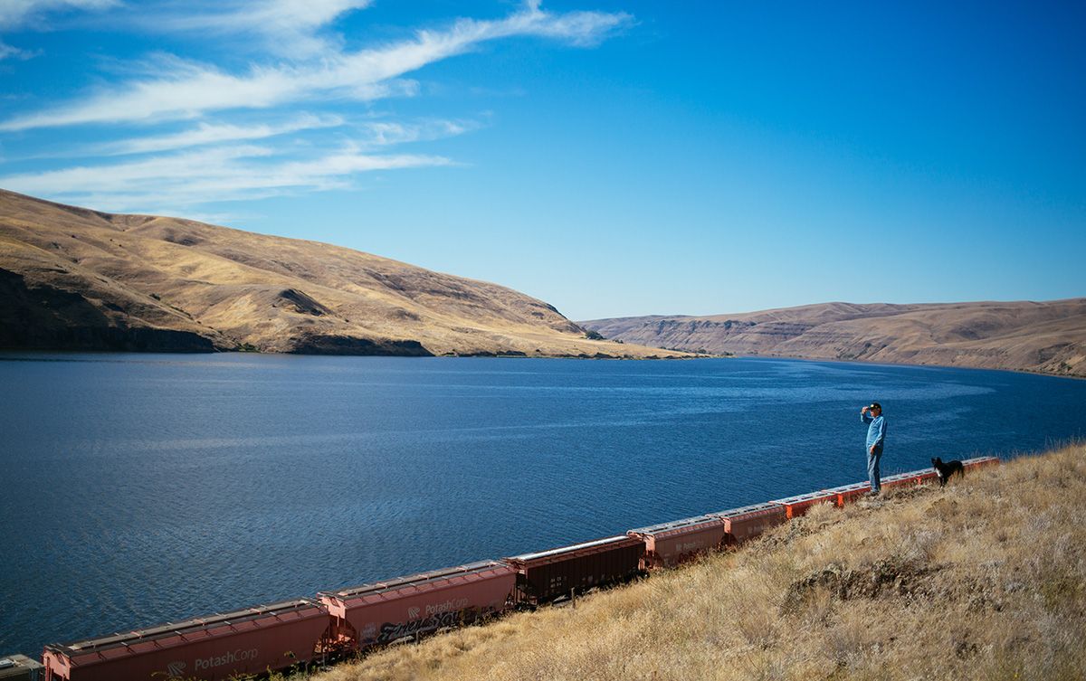 Bryan Jones, who operates one of the few family farms remaining in the community of Dusty, partway between Spokane and Clarkston, stands on a rocky outcrop above the Snake River and the railway line.