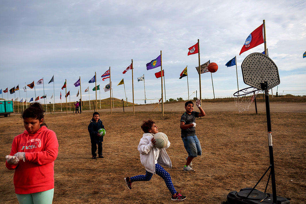 A small group of youth are playing basketball in a field. Behind them are two long rows of Tribal flags, each of a different emblem.