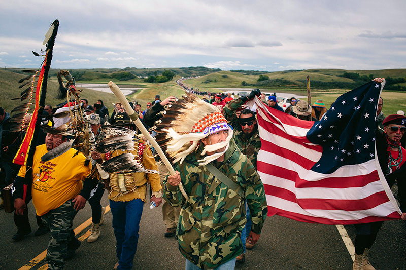 A group of protestors march on a road. In front, leading the group is Catcher Cuts The Rope. He is wearing a camouflage print jacket, a feather headdress, and carrying a swagger stick. To the right, other protestors are holding up a flag of the Unites States.  In the canton of the flag, there are single stars at the four corners and two concentric circles of stars in the middle.