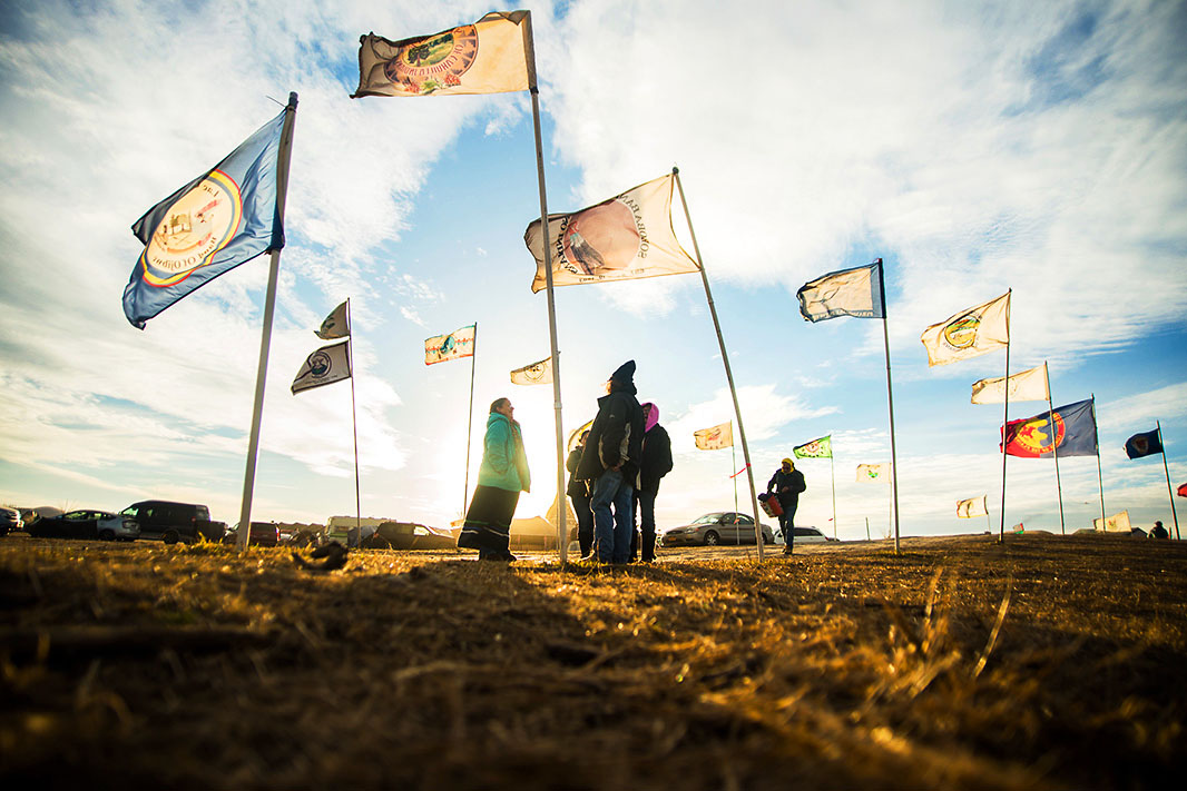 A group of people stand beside two rows of Tribal Flags at the Sacred Stone Camp, Nov. 16, 2016.