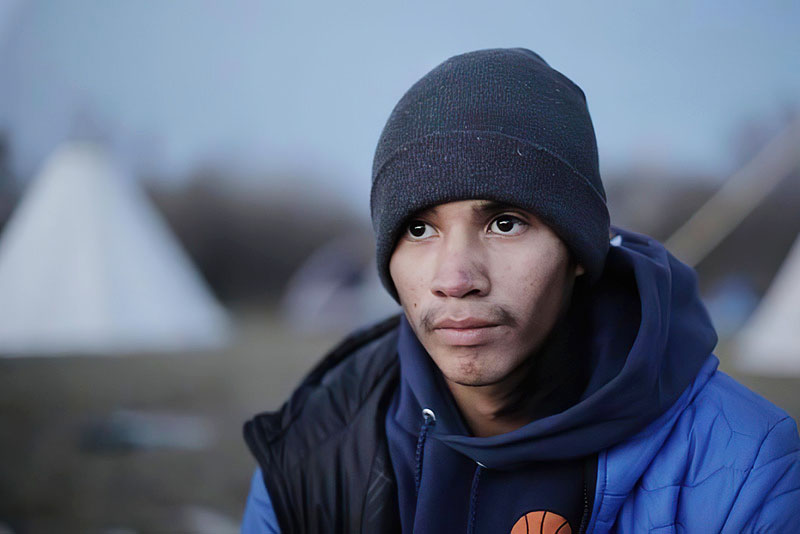 A view of Terrell IronShell's face and upper torso. He is wearing a black beanie, a blue sweatshirt, and a blue puffy jacket. He is not looking directly at the camera. In the background are multiple teepees set out on a field. The background is out of focus.