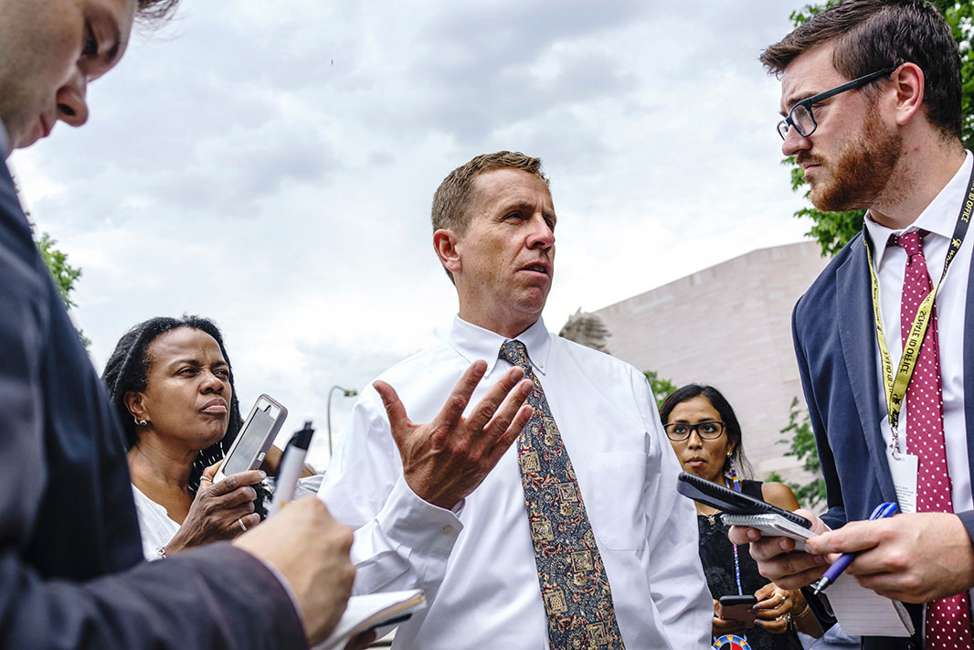 Jan Hasselman is seen outside a court building talking to others. He is wearing a white shirt with a multicolored patterned tie. Those listening around him are writing on notepads and holding out their phones as if recording Jan.