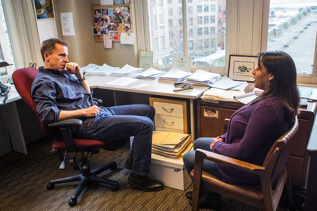 In a corner office with windows, sits Jan Hasselman on the left and Stefanie Tsosie on the right. Hasselman is in a red office  swivel chair. He has short blonde hair and is dressed in a blue button up long sleeve, denim pants, and leather shoes. He has one arm resting on the arm rest and another held up close to his face. Stefanie sits facing Jan in  chair made of wood and leather. She is wearing a purple knit sweater, denim jeans, and leather boots. She has shoulder length brunette hair and her mouth is open as if speaking to Jan. Beside them are stacks of paper atop a desk and cabinet. On the floor, beside their feet is a box with a stack of files on top. The view from the window shows that they are multiple stories up. Hung on the walls are a calendar, and a pushpin board with photos.