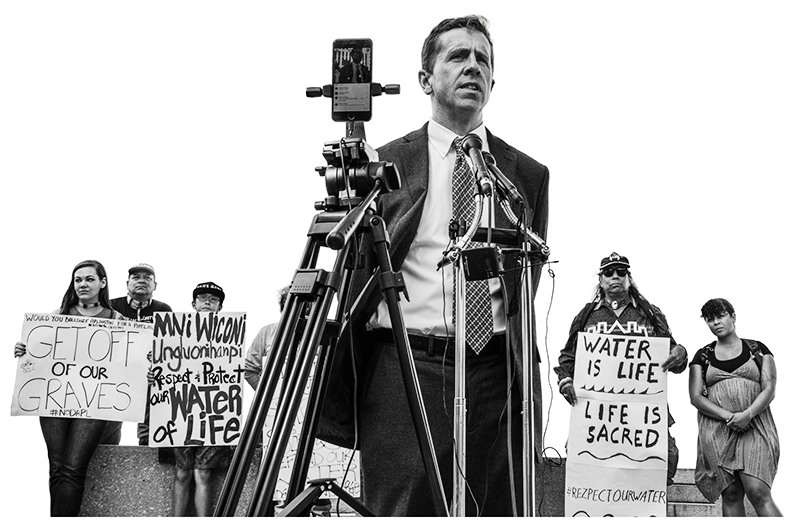 A black and white image of Jan Hasselman standing in a suit in front of a microphone. A phone is set on a tripod filming him. Behind him are protestors holding signs that say 'Get off of our graves. #noDAPL,' 'Mní Wičóni ungluonihanpi. Respect & Protect our water of life,' and 'Water is life. Life is sacred. #rezpectourwater