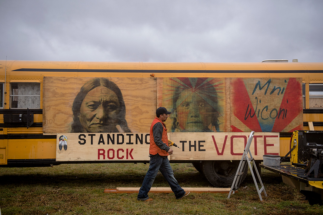 Wooden plywood boards are mounted on the side of a yellow bus. Portraits of native faces, and the words 'Mní Wičóni' (Water is Life) are painted on the boards. Below these are a sign that says 'Standing Rock. The Vote.' A man dressed in a black brimmed cap, an orange vest, denim pants, and heavy-duty boots is walking in front of these signs with a power drill in hand. There are wooden planks on the floor, a step ladder, and a container of bits set atop the open tailgate of a yellow truck.