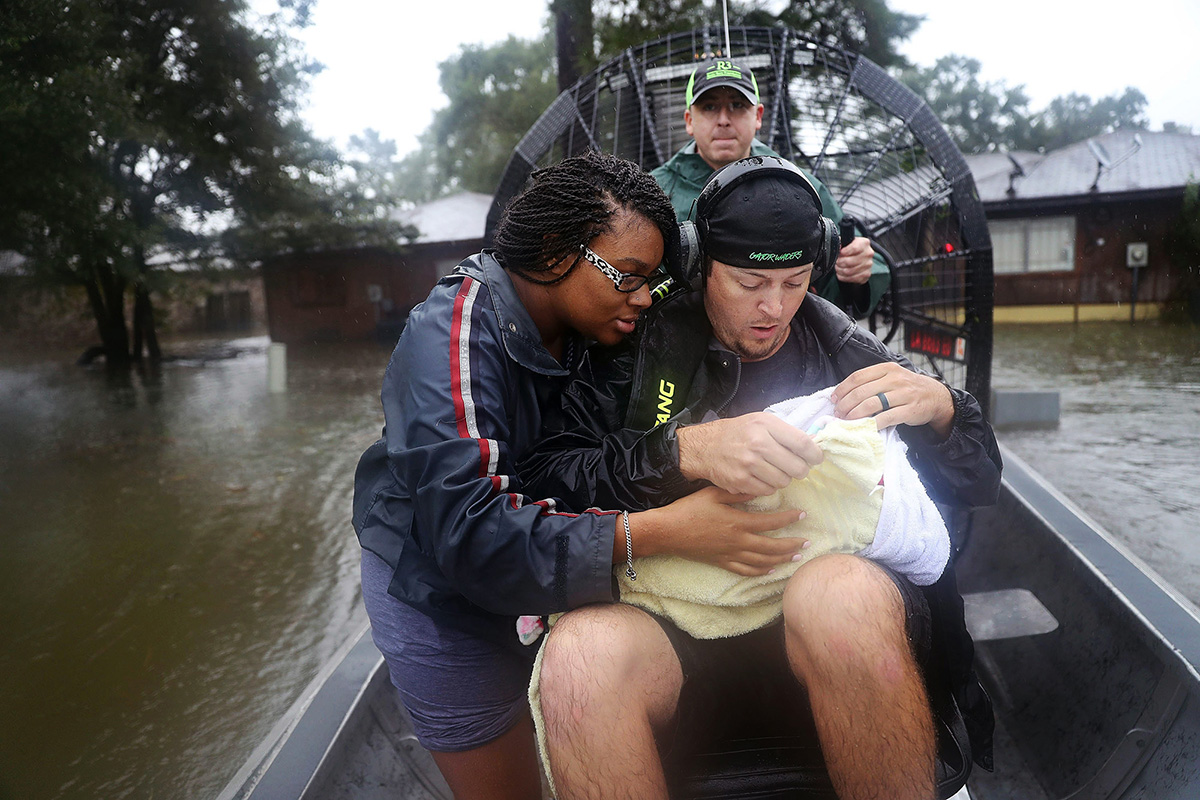 A mother and her 3-week-old baby are ferried from their home amidst the floodwaters of Hurricane Harvey in 2017.