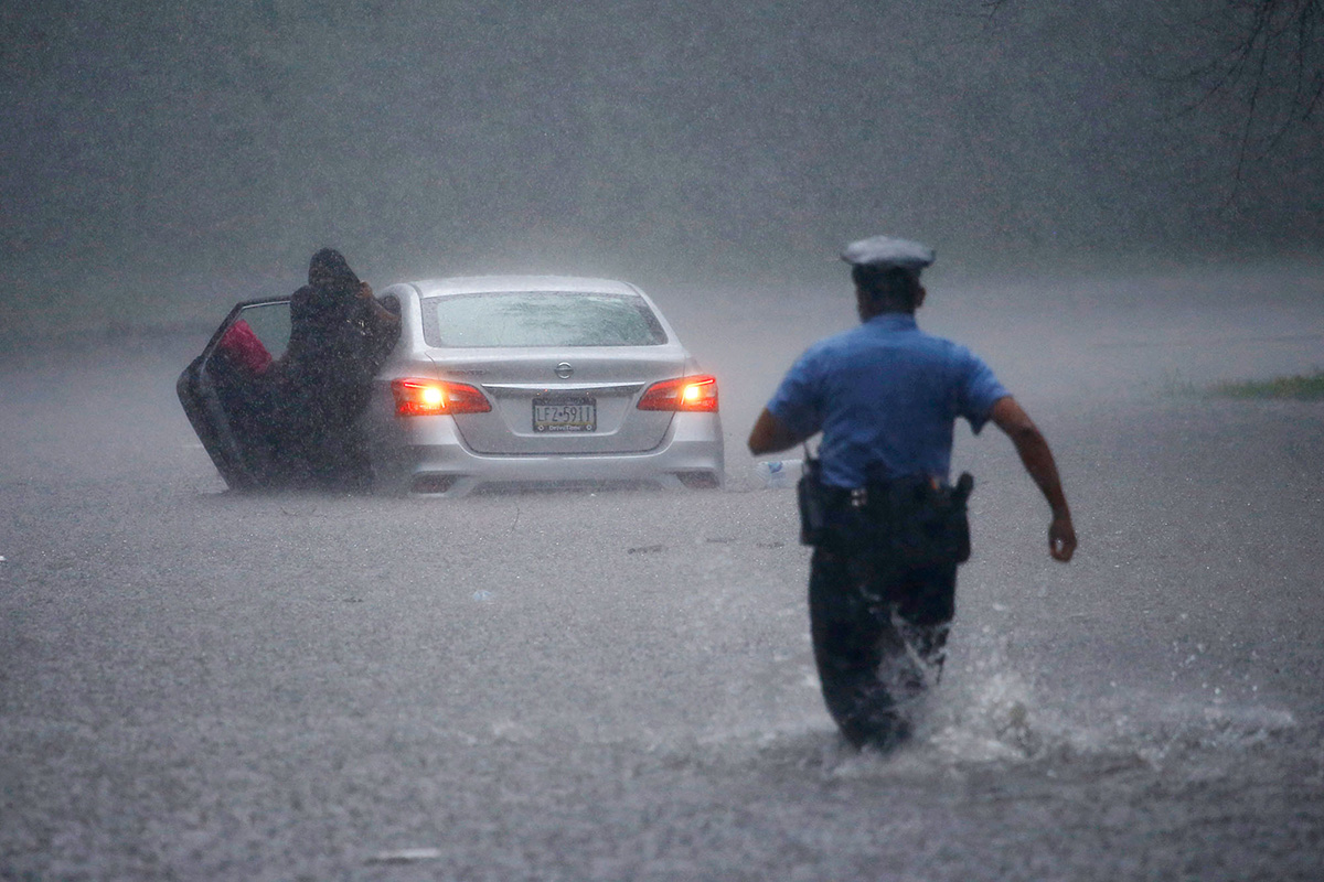A Philadelphia police officer rushes to help a stranded motorist during Tropical Storm Isaias, Aug. 4, 2020.