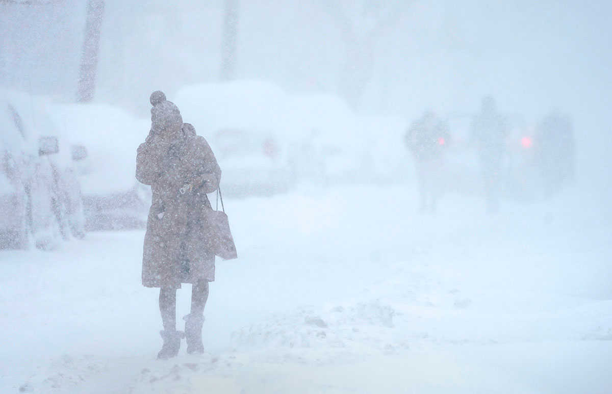 A woman tries to protect her face from blowing snow while walking in white-out conditions in Jersey City, N.J., Monday, Feb. 1, 2021. The winter storm dropped more than two feet of snow on the area and may have broken a 122-year-old  snowfall record for the state.