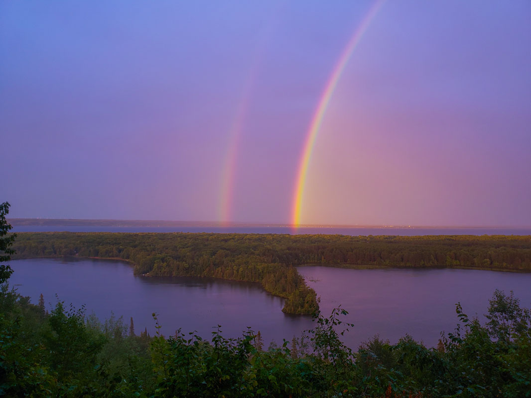 Double rainbows in the sky, from Mission Hill Overlook, overlooking Bay Mills Indian Community with Spectacle Lake and Lake Superior in the background.