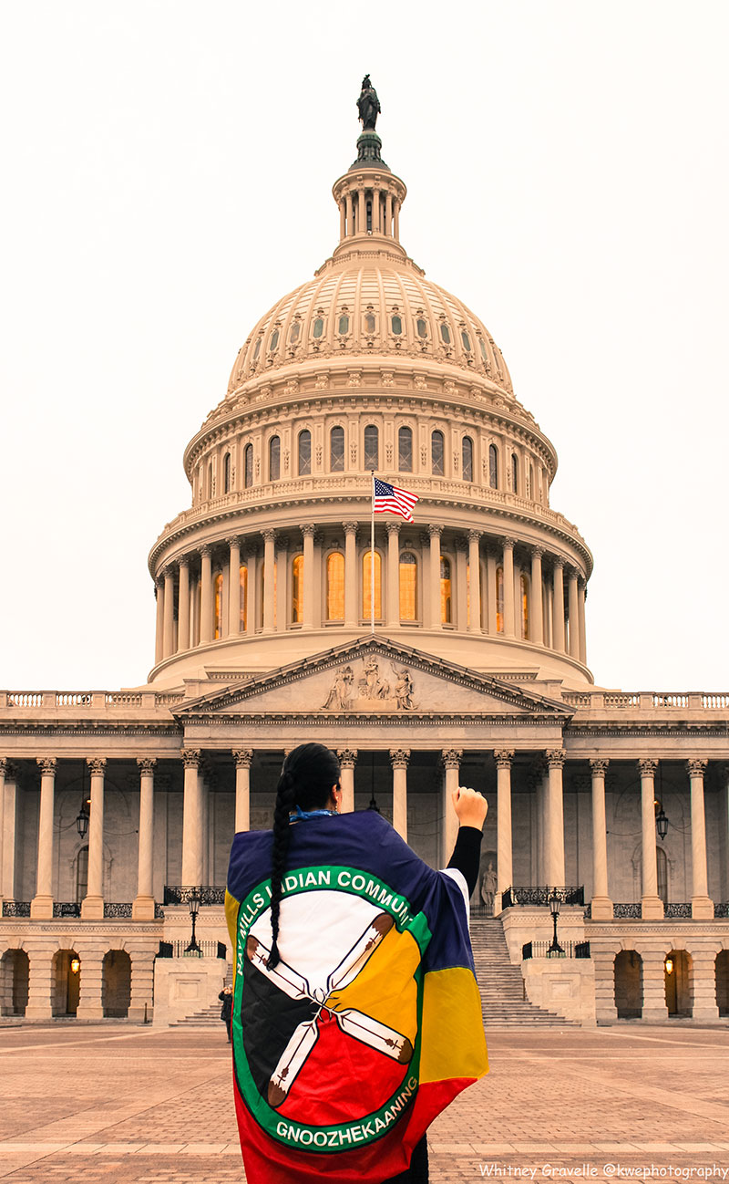 Whitney Gravelle standing in front of the Capitol building at the Women's March protest in Washington, D.C., in January of 2017. Bay Mills Indian Community flag wrapped around her back, and right fist raised to the air.