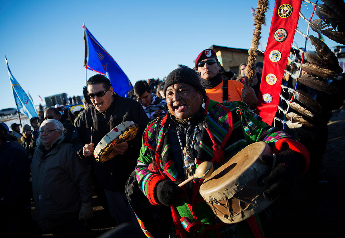 Dan Nanamkin, of the Colville Nez Perce Native American tribe in Nespelem, Wash., right, drums with a procession through the Oceti Sakowin camp in Cannon Ball, N.D., Dec. 4, 2016.