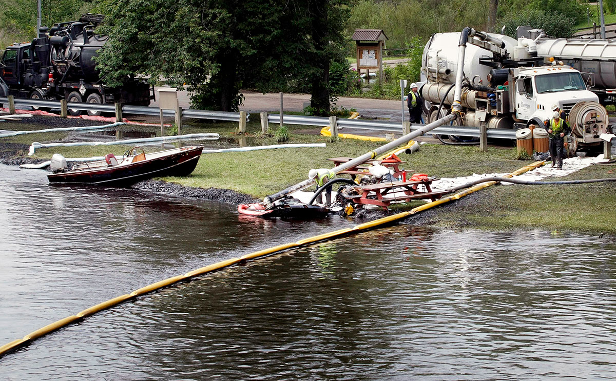 Workers use suction hoses try to clean up an oil spill from the Kalamazoo River on Jul. 28, 2010 in Battle Creek, Mich.