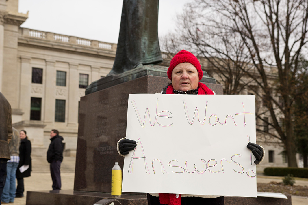 A woman in West Virginia holds a sign, symbolizing what many residents are asking for.