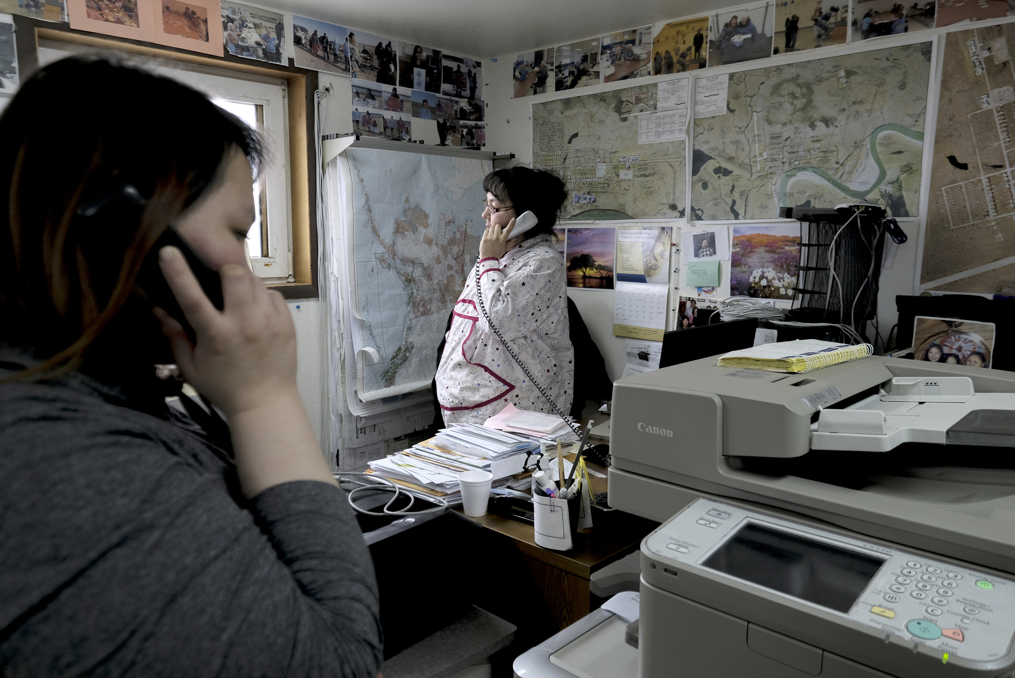 Martha Itta (center) takes calls in her office in Nuiqsut on May 30, 2019.