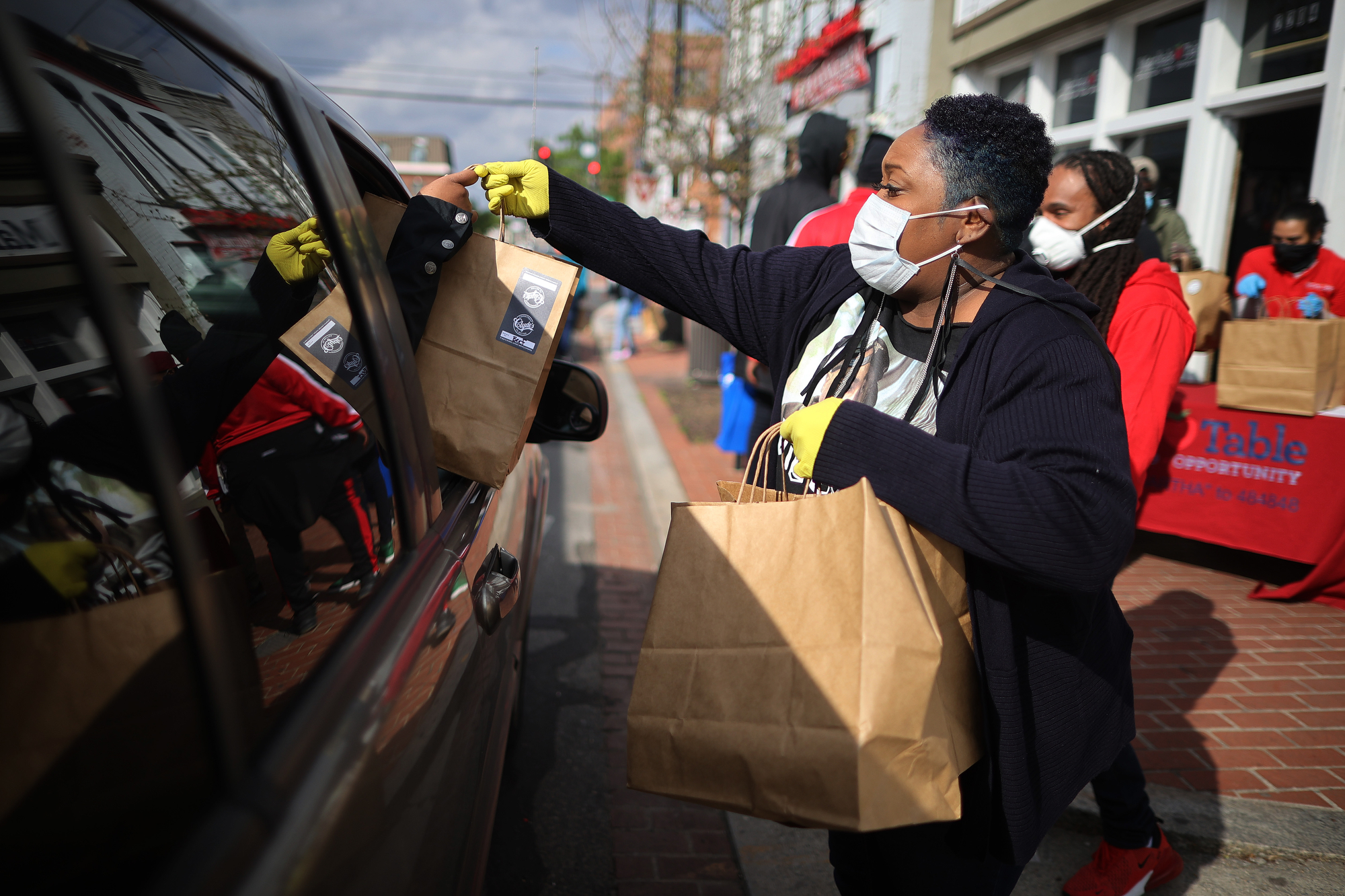 A volunteer at a nonprofit in Washington, D.C., distributes free hot meals during the COVID-19 pandemic.