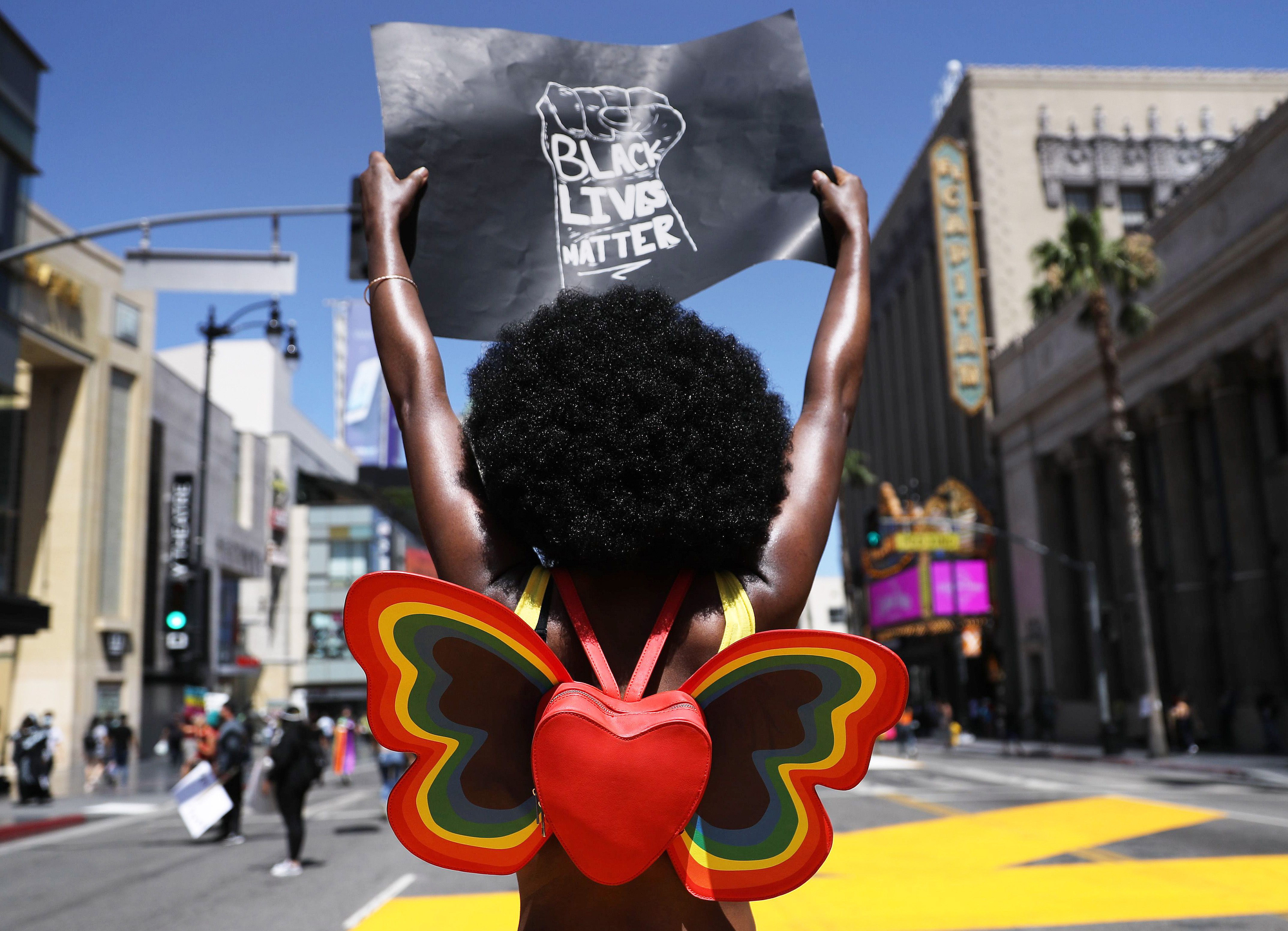 A protester strikes a pose while holding a 'Black Lives Matter' sign on Hollywood Boulevard during the All Black Lives Matter solidarity march on June 14, 2020 in Los Angeles.