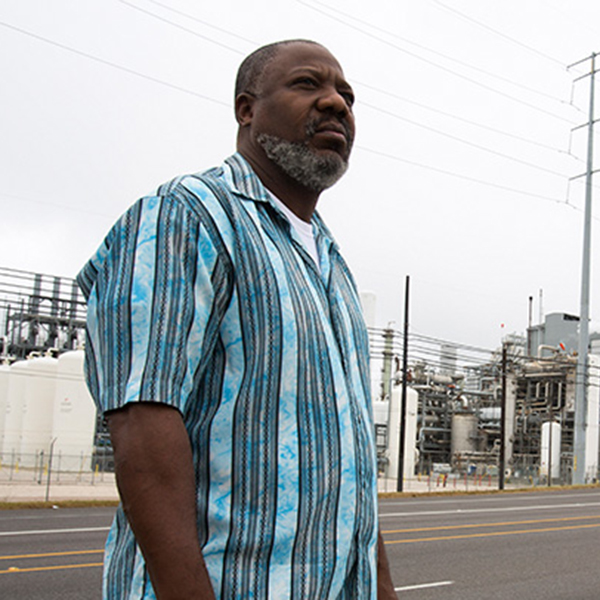 Hilton Kelley stands before the Valero refinery in Port Arthur, TX