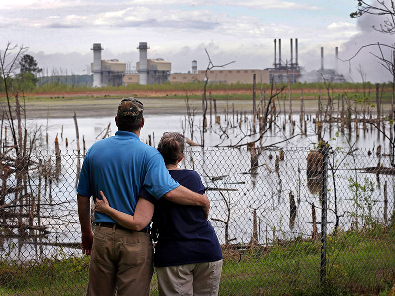 A couple look from their yard across an ash pond full of dead trees toward Duke Energy's Buck Steam Station in North Carolina.