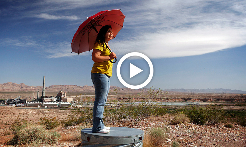 Vickie Simmons stands on a hill in between the Reid Gardner Power Plant in Nevada and her home on the Moapa River Reservation.