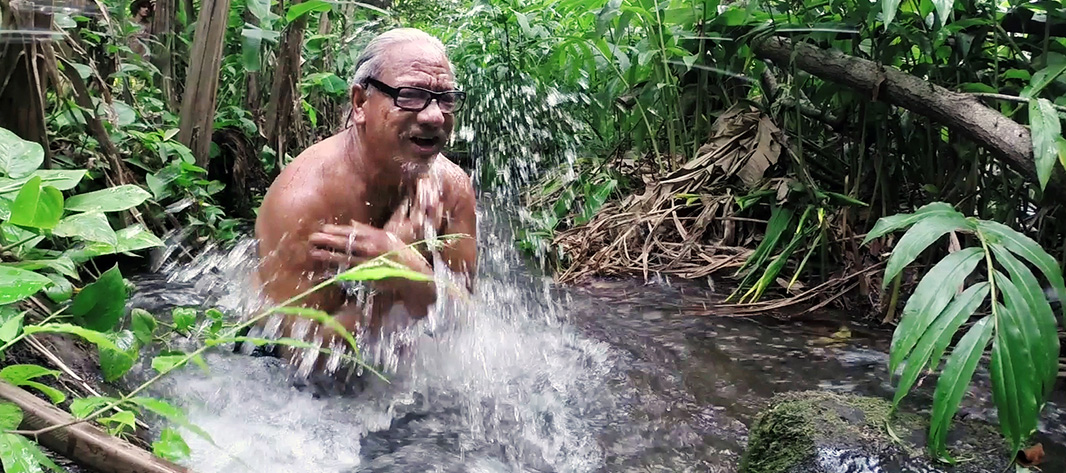 Local citizen Walter Kanamu jumps into Wailuku River to celebrate the return of stream flows.