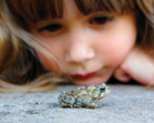 Small child with amphibian. (iStockphoto)