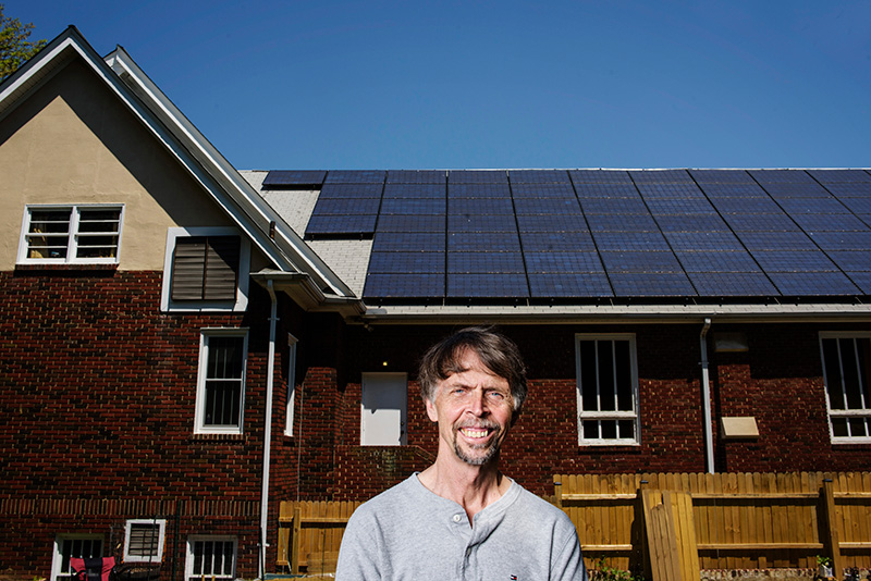 David Brosch, President of the University Park Community Solar, LLC, stands in front of a 22 kilowatt solar electric array atop the roof of the University Park Church of the Brethren in University Park, Maryland on May 4, 2015. The solar panels on top of the church produces an estimated 25% more energy than the church needs per year. Members of the LLC who helped pay for the solar panels receive dividends based on the money they invested.