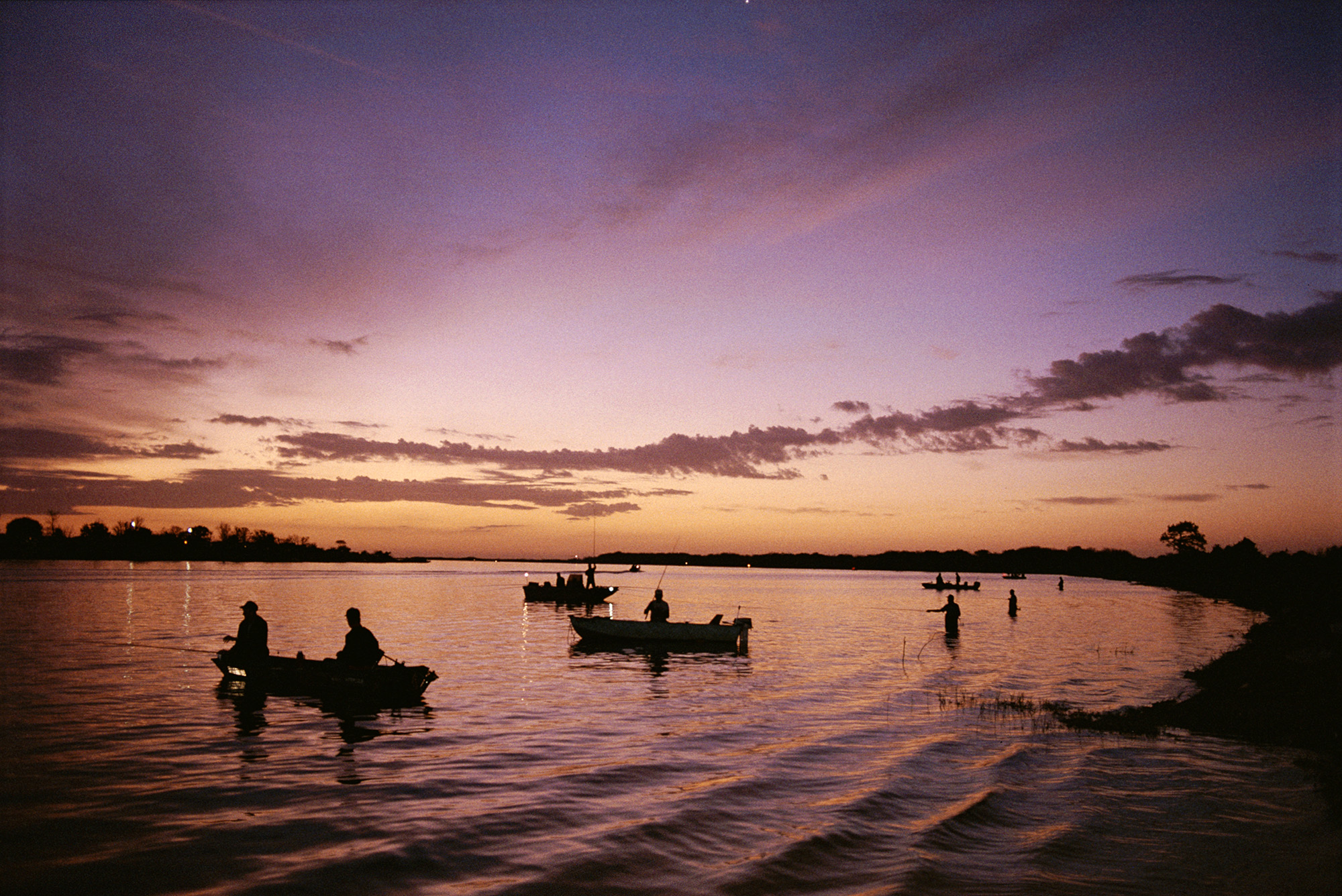 People fish on Florida's Kissimmee River at sunset.