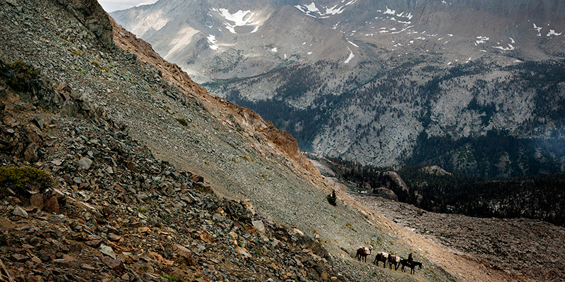 National Park Service employees headed for Big Arroyo lead a pack of horses over Black Rock Pass. The Kaweah Peaks Ridge is in the background. Note the distinct transitions in the rock from black to red.