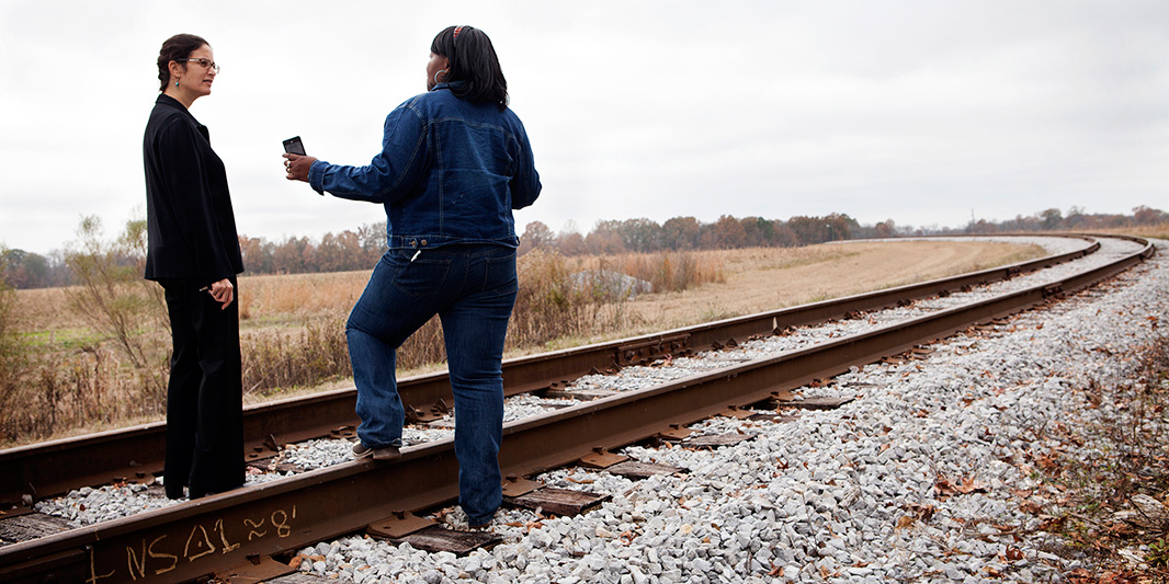 Senior Staff Attorney Marianne Engelman Lado (left) and client Esther Calhoun stand on  the train tracks that brought four million cubic yards of toxic coal ash to Perry County, predominantly African-American and one of the lowest-income in Alabama.