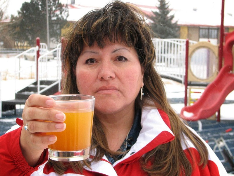 A member of the Fort Belknap Indian Community holds a glass of contaminated water from the Zortman-Landusky mines.