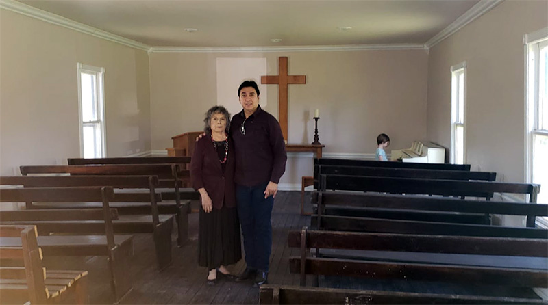 Paul Villarreal, Jr., and his mother in the interior of the Jackson Ranch church, during a worker appreciation luncheon at Jackson Ranch Cemetery. One of the tribal members' children is at the piano.